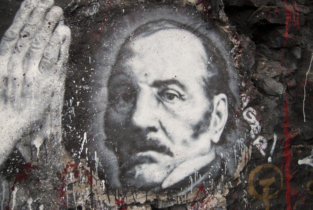 Um grafite/desenho de Allan Kardec em um muro de pedra.