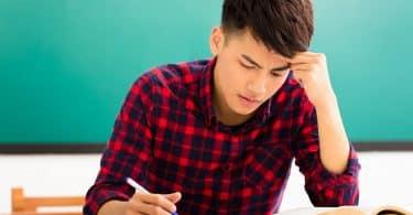 Um homem escrevendo em um caderno numa mesa. Ele parece estressado.