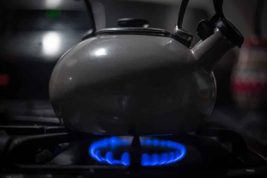 Um fogão com fogo baixo aquecendo uma chaleira.