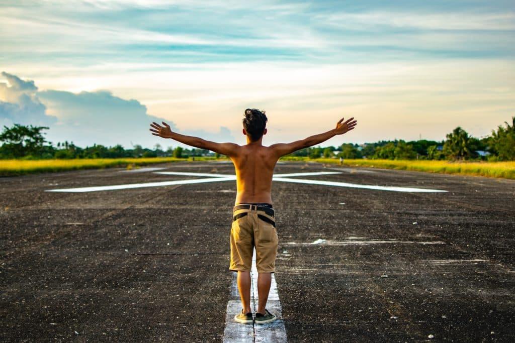 Homem branco de braços abertos numa pista de vôo.