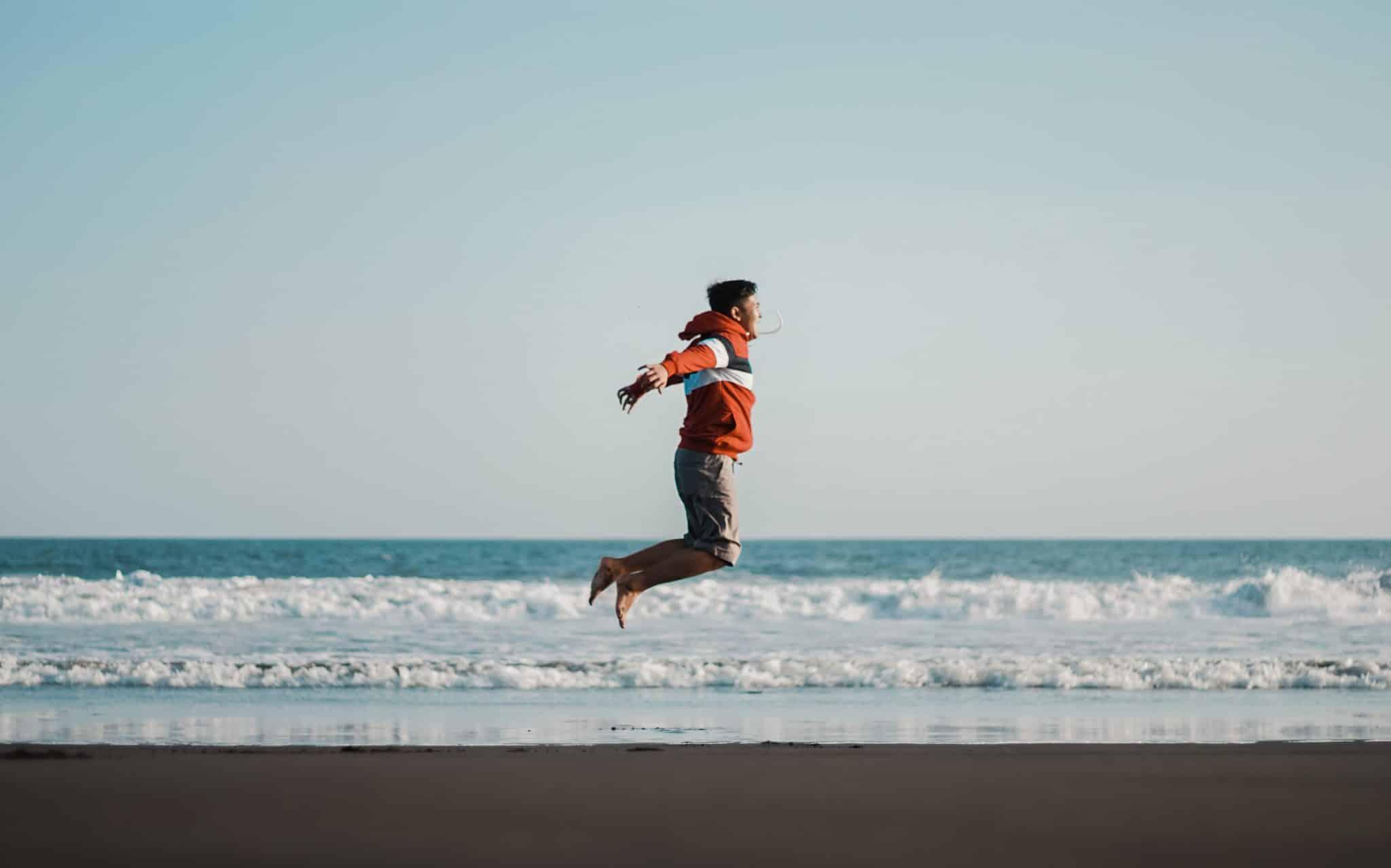 Um homem pulando em uma praia. Em plano posterior, o mar.