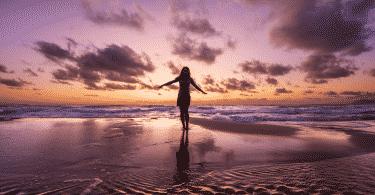 Mulher de braços abertos na praia durante o pôr do sol