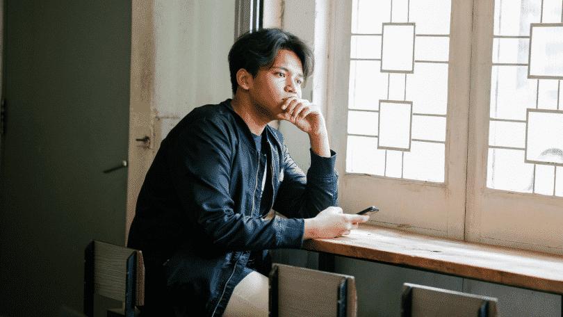 Homem olhando pensativo para a janela