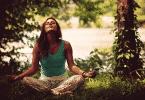 Mulher meditando sentada na grama
