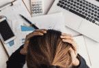 Mulher estressada no escritório com as mãos na cabeça