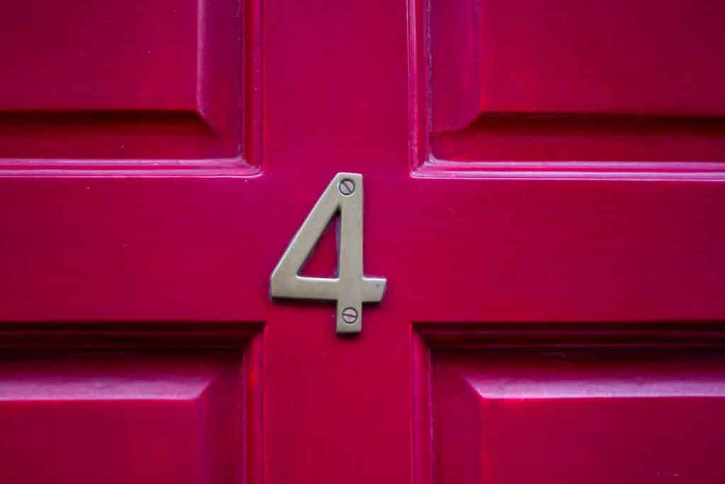 Número quatro em uma porta rosa.