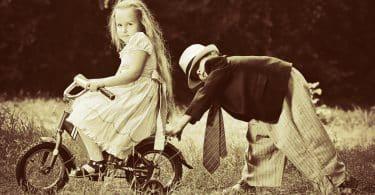 Menina e menino brancos brincando de bicicleta num campo.