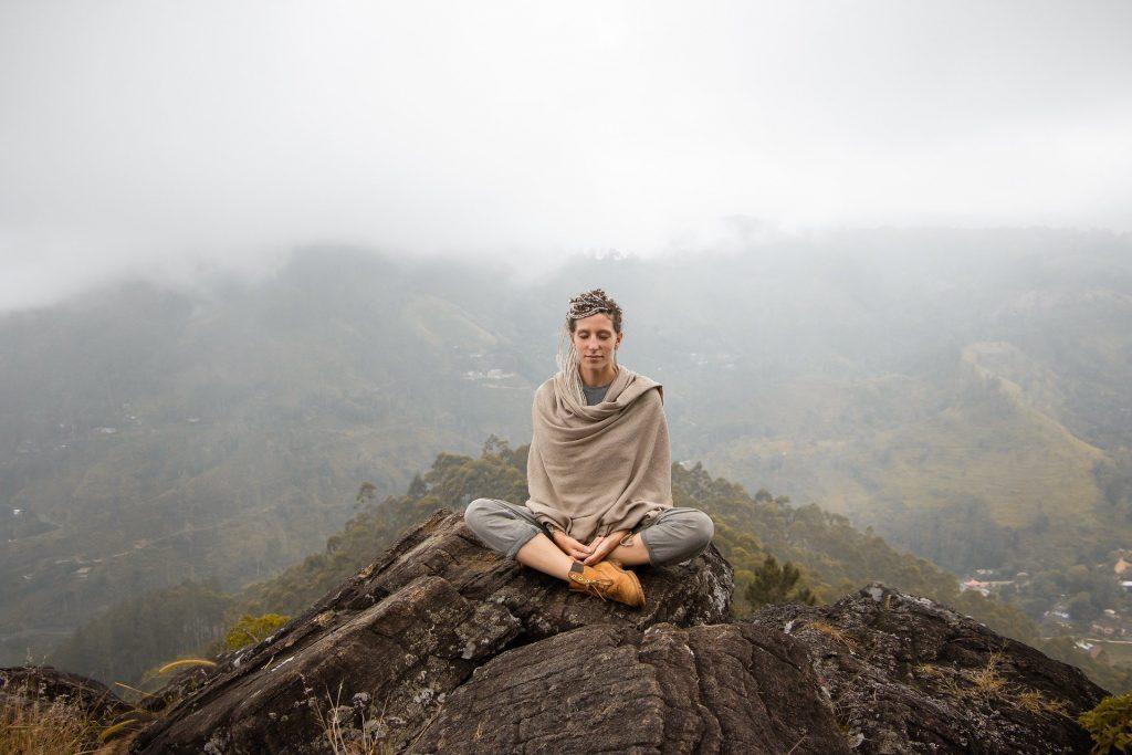 Uma mulher branca sentada num pico montanhoso. No entorno, uma forte neblina, também sobre a região montanhosa.