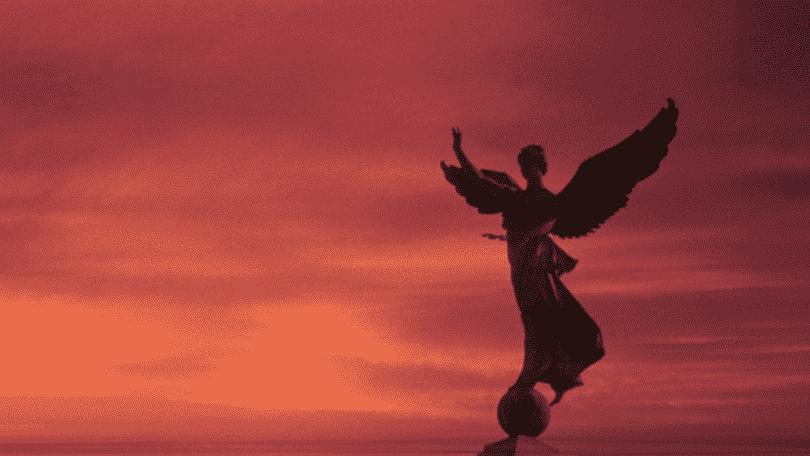 Silhueta da estátua de um anjo na frente do céu quase escurecendo