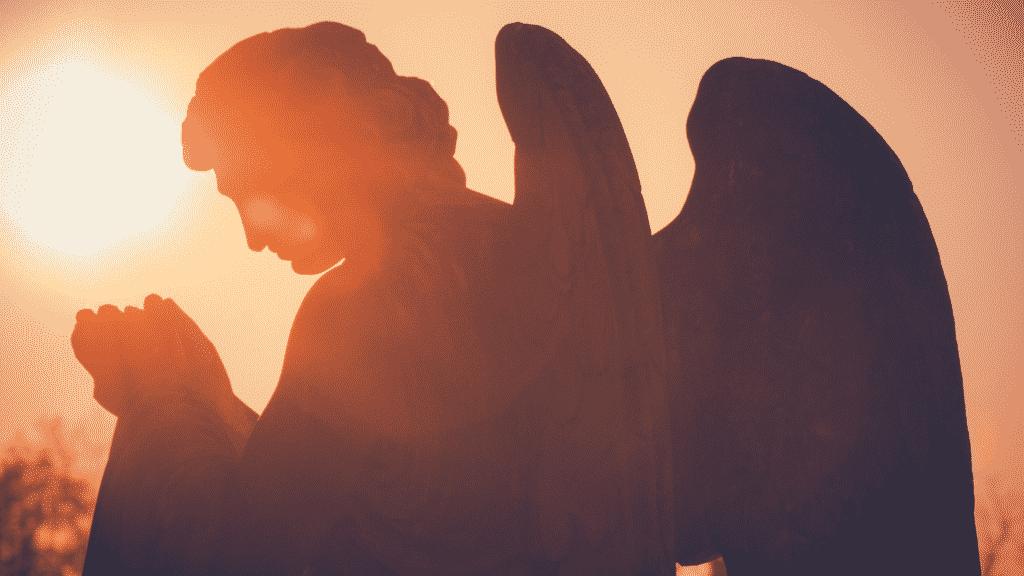 Silhueta de uma estátua de anjo de lado, com as mãos juntas e em sinal de oração