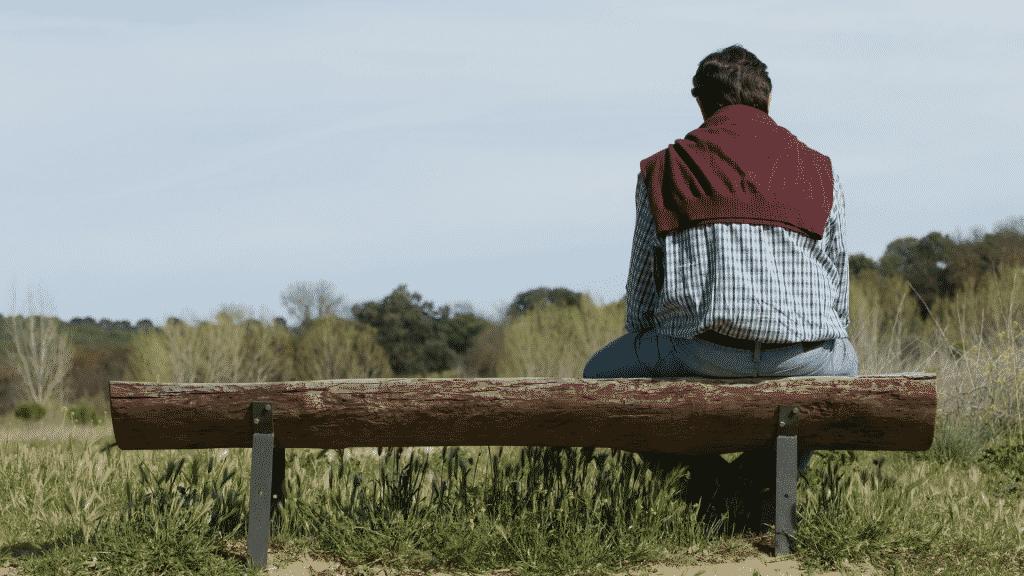Homem sentado em banco de madeira, observando um campo com árvores