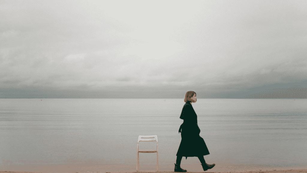Mulher caminhando na beira de uma praia. No centro da foto, uma cadeira vazia na areia