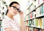 Mulher em uma biblioteca com olhar reflexivo e com uma mão ajustando o óculos