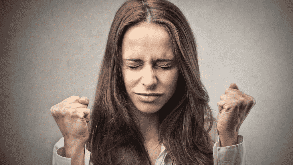 Mulher de olhos e mãos fechadas, com expressão de estar sentindo raiva
