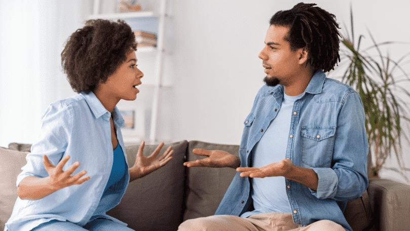 Homem e mulher sentados em um sofá, discutindo