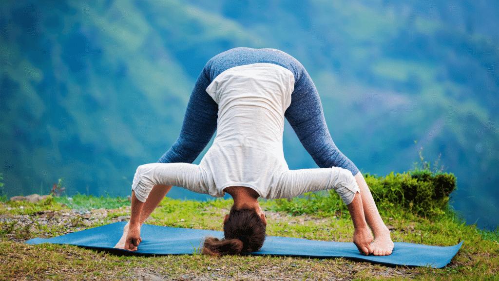 Mulher em um campo praticando posição da yoga Ashtanga