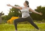 Mulher praticando posição de yoga em um campo aberto