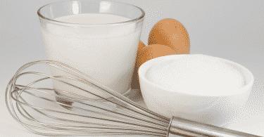 Leite em um copo de vidro, ovos, açúcar e um batedor manual de ovos sobre uma mesa