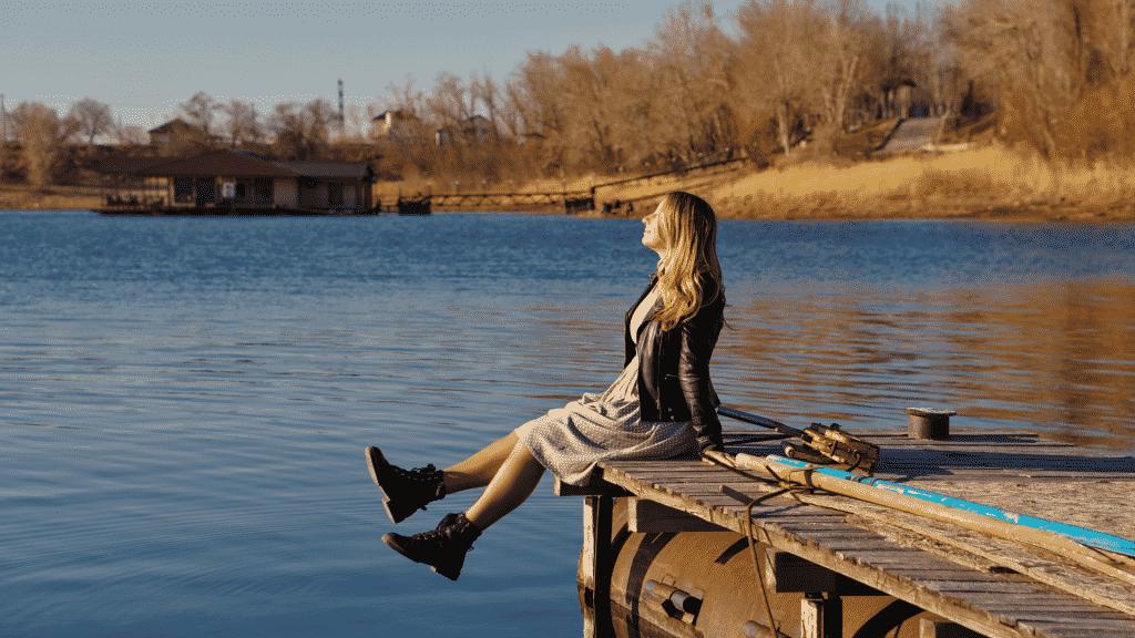 Imagem de uma mulher sentada em um deck de madeira, na beira de um rio