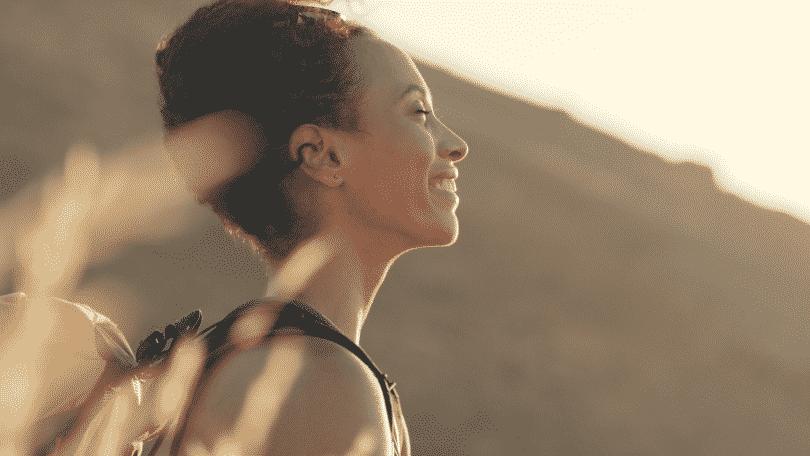 Mulher sorrindo e de olhos fechados, sentindo o sol em seu rosto