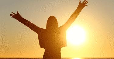 Mulher de braços abertos, recebendo a luz solar