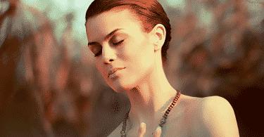 Mulher de olhos fechados e mão no peito, com expressão de concentração