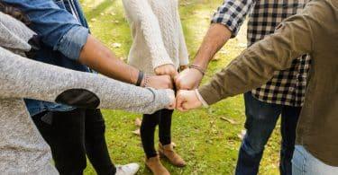 Várias pessoas se cumprimentando. Elas tocam seus punhos uns nos dos outros.