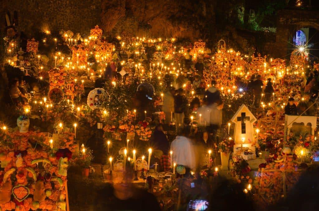 Noite dos Mortos em Janitzo. Várias pequenas velas dispersas, algumas lápides e plástico e algumas caveiras, todas também dispersas.