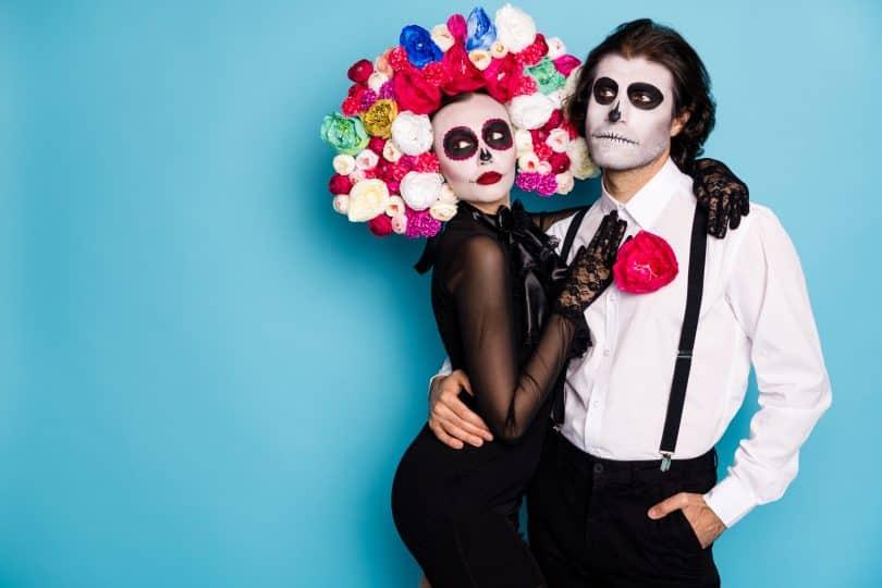 Um homem e uma mulher abraçados e fantasiados com trajes típicos do Día de Los Muertos Mexicano