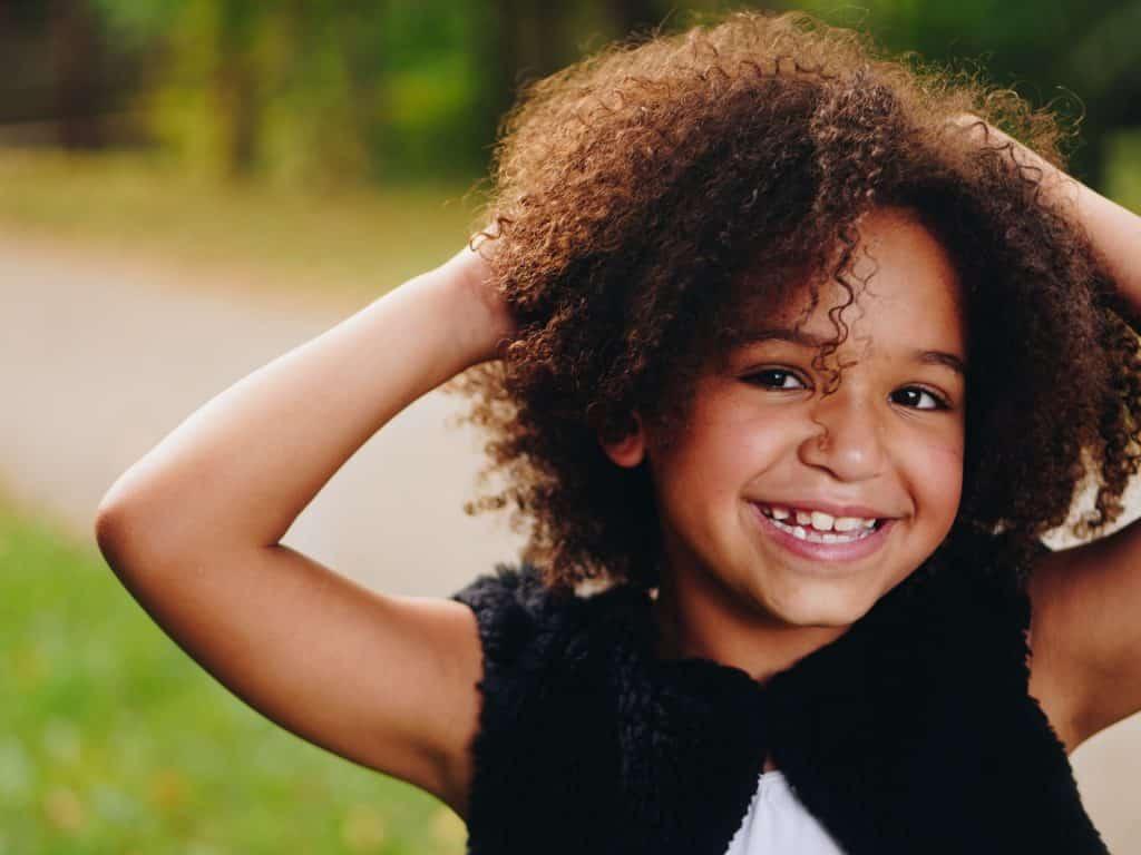 Menina negra sorrindo e com as mãos no cabelo.