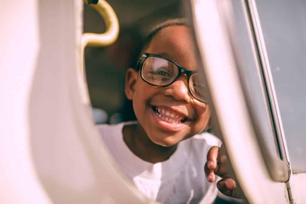 Menino negro de óculos sorrindo.