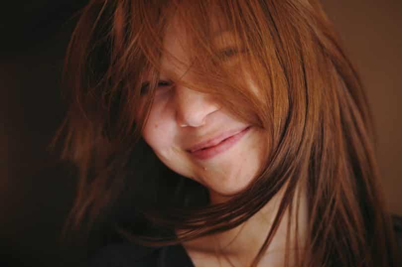 Jovem branca com cabelos ruivos no cabelo.