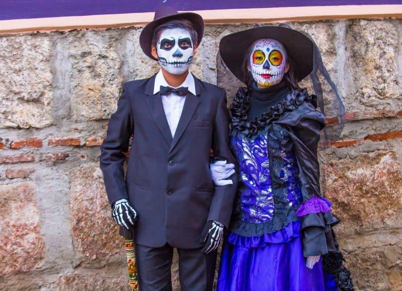 Um homem e uma mulher fantasiados para o Día de Los Muertos.