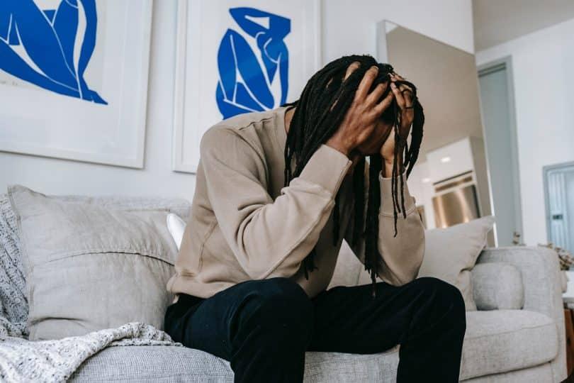 Homem negro com a cabeça baixa e as mãos na cabeça.