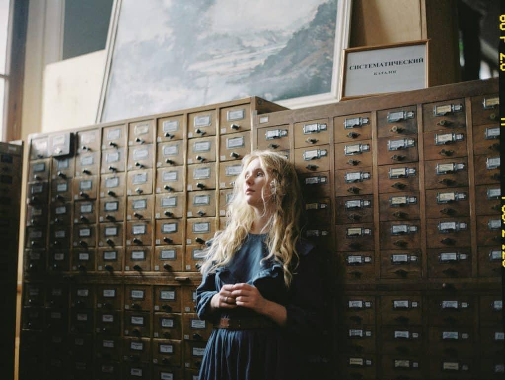 Menina encostada em uma parede, olhando vagamente para o lado.