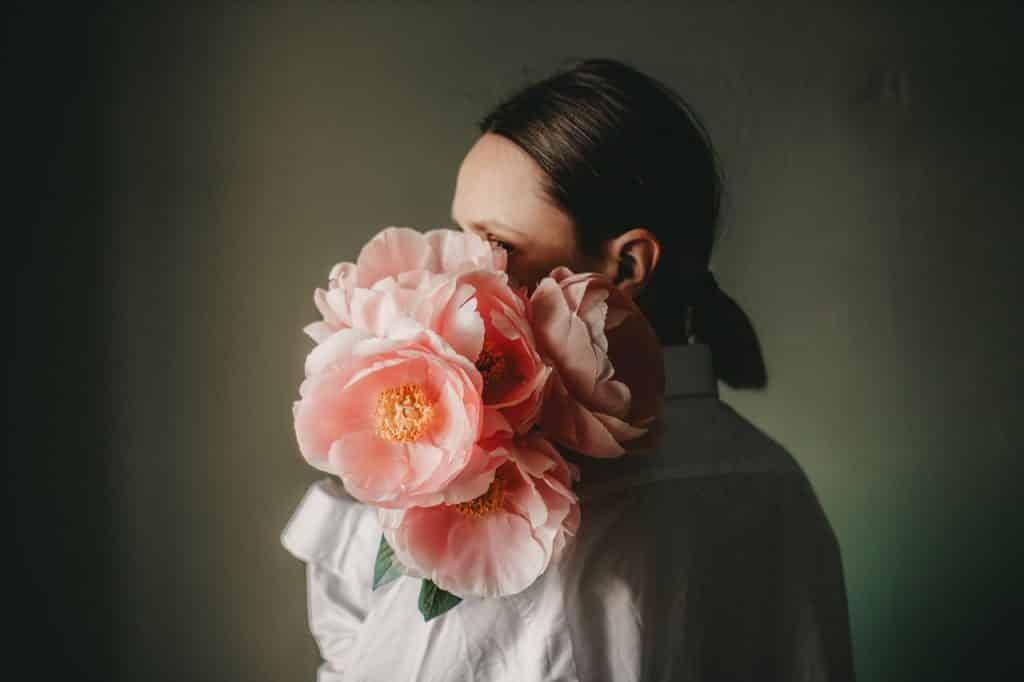 Mulher branca segurando flores rosas.