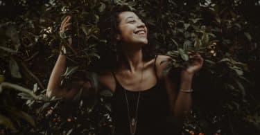 Mulher negra sorrindo em meio a folhas.