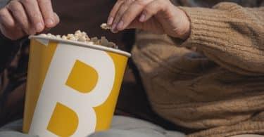 Um casal assistindo filme e comendo pipoca juntos