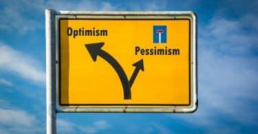 Uma placa com os seguintes elementos gráfico-visuais: 'pessimism' à esquerda, com uma seta à esquerda; com uma seta à direita, 'otimism'.