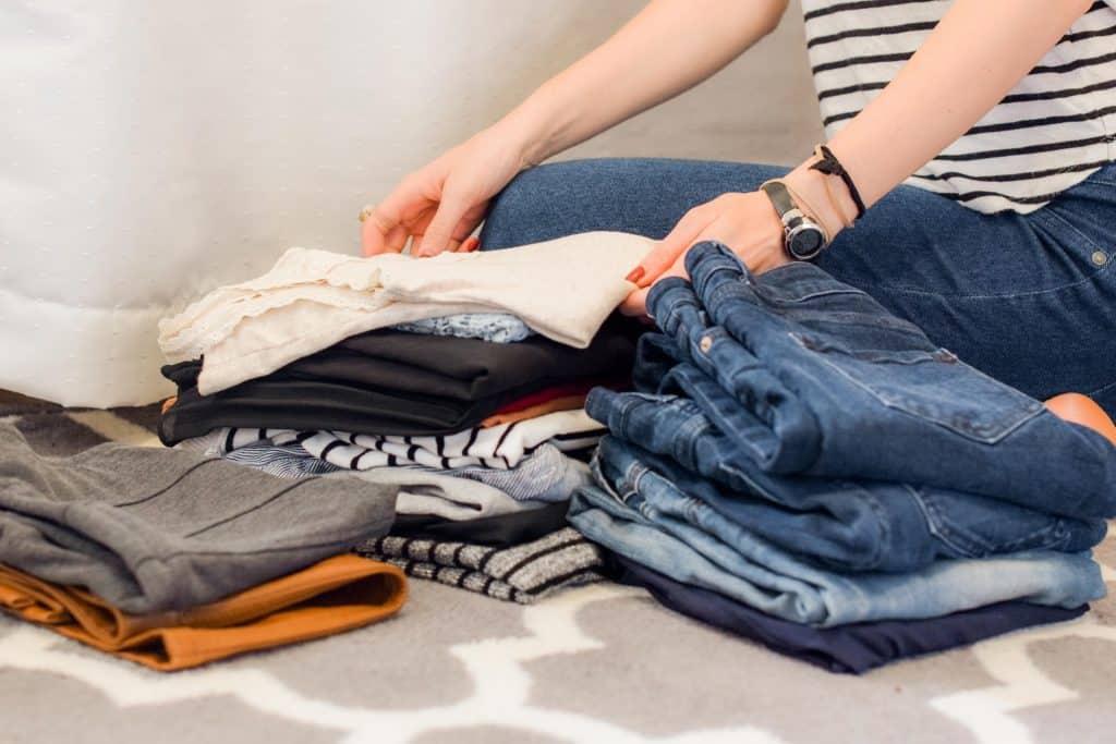 Mulher branca organizando roupas.